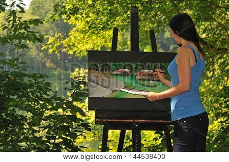 young woman working on acrylic painting outside by the water