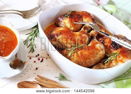 Roast chicken with sauce and rosemary in ceramic tableware