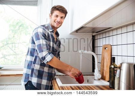 Happy young man in plaid shirt standing and washing dishes on the kitchen