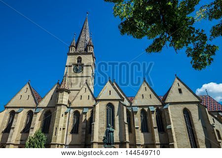 Georg Daniel Teutsch monument in front of Saint Mary Lutheran Cathedral in Sibiu city in Romania poster