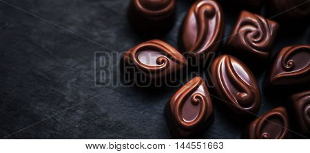 Delicious chocolate candies background. Assortment of delicious chocolate pralines with different shapes