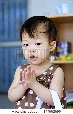 Thai baby in brown dress standing with hands clasped (Sawasdee - Thai greeting) in the room. identity culture of Thailand