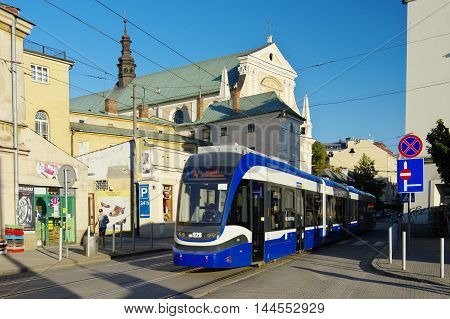 Krakow Poland - August 25 2016 Karmelicka street. Tram on the street behind him Carmelite Church.
