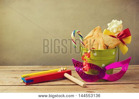 Hamantaschen cookies in bucket with grogger noise maker and carnival mask. Gift for purim festival