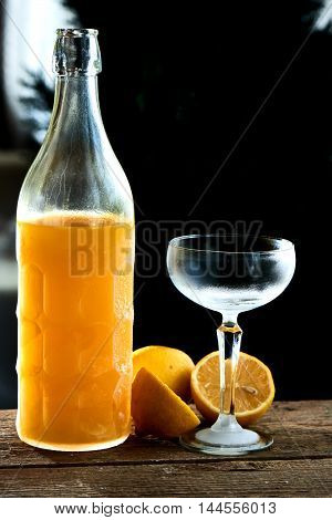 Alcoholic cocktail Limoncello sauer served in a glass wine glass and bottle on wooden table on black background