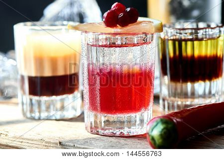 Set of alcoholic cocktail consisting of B-52, the pupil of a Nazi and boyarsky in glasses on a wooden table