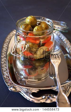 Pickled Brussels sprouts with vegetables in glass jar