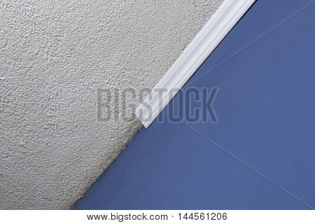 Installing crown molding on ceiling in room with painted wall. Fragment of molding horizontal view. Home improvements