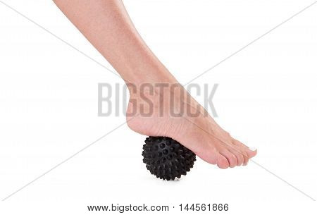 Massage feet with a rubber black spiky ballin on an isolated white background.