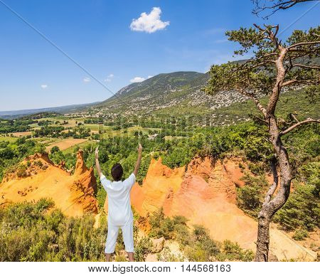 The elderly woman performs yoga in special form. Orange and red picturesque hills in Roussillon