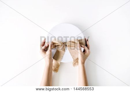 white gift cardboard box with brown bow and girl's hands on white background. flat lat top view