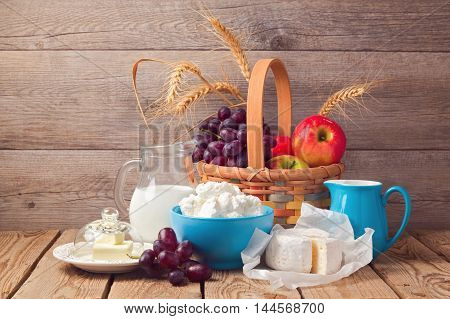 Milk cheese and fruit basket over wooden background. Jewish holiday Shavuot celebration