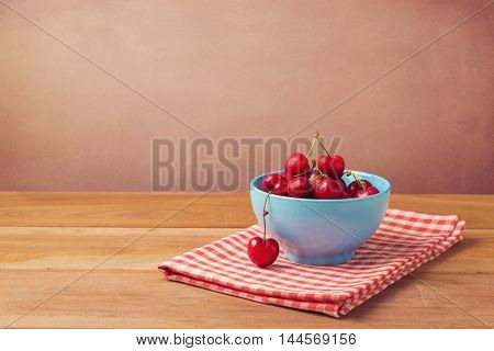 Fresh red cherries over wooden background with red checked tablecloth