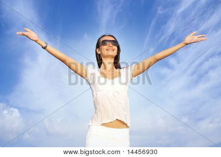 Portrait of young happy woman over sky background
