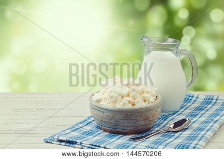 Milk and cottage cheese over green bokeh background. Jewish holiday Shavuot concept