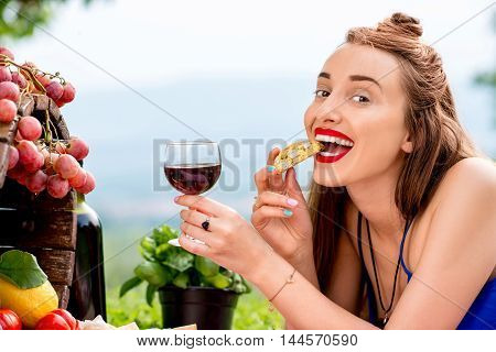 Beautiful woman tasting cantuccini cookie lying on the grass with lots of tasty italian food and wine in the countryside in Tuscany. Cantuccini is traditional italian almond cookie