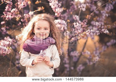 Smiling kid girl 4-5 year old holding flower wearing purple scarf and gray stylish sweatshirt over blooming tree outdoors. Looking at camera. Childhood. Spring portrait.