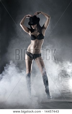 Sexy woman in erotic lingerie over dark background with smoke