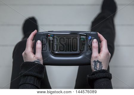 Gothenburg, Sweden - February 20, 2016: A shot from above of a young woman's hands holding a Sega Game Gear, a handheld video game console developed by Sega Games Co., Ltd. in the 1990s.