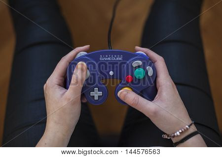 Gothenburg, Sweden - January 25, 2015: A shot from above of a young woman's hands holding a purple game pad controller for the Nintendo GameCube video game console developed by Nintendo Co., Ltd.