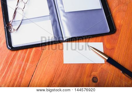 Open business card holder with business cards and a pen are on the table