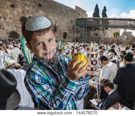 Charming seven year old boy in white festive skullcap with etrog. Sukkot at the Western Wall of Temple in Jerusalem