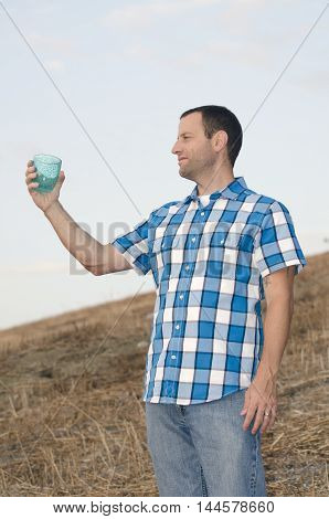 Cheers! Man looking out on a hill side while holding a cup with his arm extended wearing a plaid shirt.