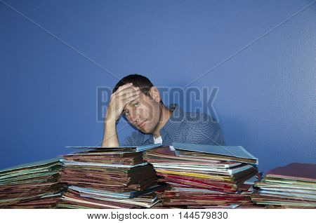 Overworked business man. Man with hand on his forehead at work with piles of files in front of him.