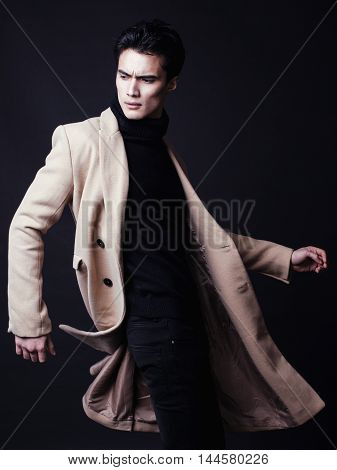 cool real young man in coat on black background posing, flying pose