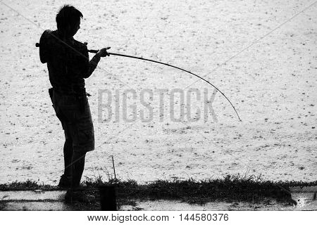 In spite of heavy rain a man is fighting fish with a fishing rod in front of water dotted by rain drops.