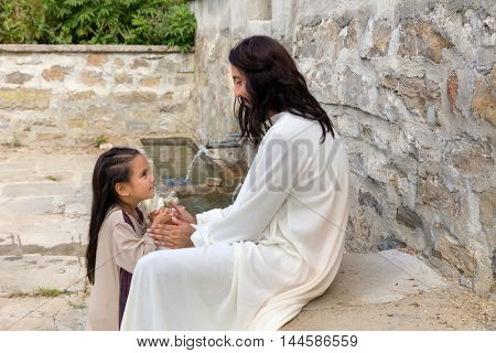 Biblical scene when Jesus says, let the little children come to me, blessing a little girl. Historical reenactment at an old water well.