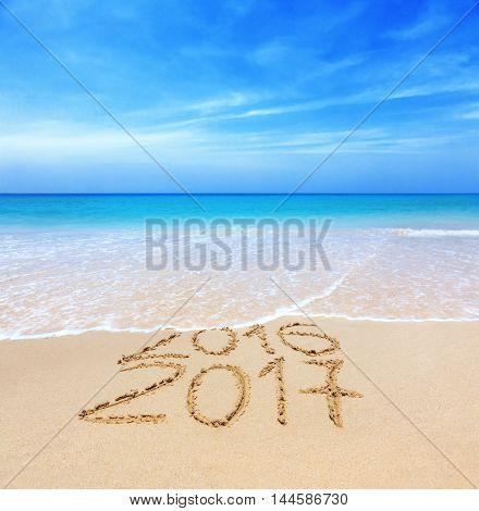 2016 and 2017 on a beach sand