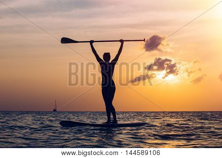 Sportive woman practicing stand up paddleboard at sunset