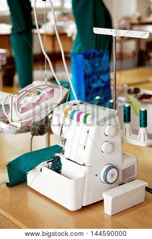 Overlock sewing machine in tailor office. Fashion designer equipment serger in a sewing workshop. Green mannequins on the background