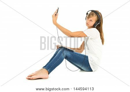 Young girl sitting on the floor taking a selfie with headphones over white background