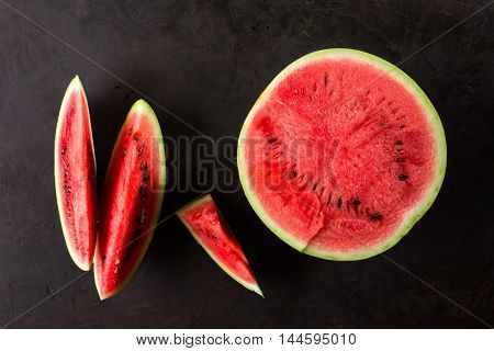 Sliced ripe watermelon on black background. top view