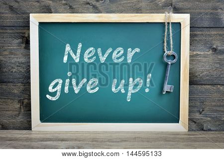 Never give up text on school board and old key