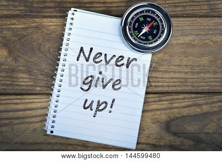 Never give up text and metallic compass on wooden table
