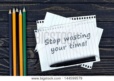 Stop wasting your time text on notepad and office tools on wooden table