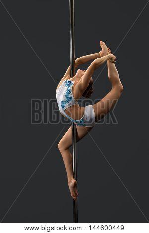 Image of modern dancer performing gymnastic split on pylon
