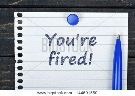 You;'re fired text on page and pen on wooden table