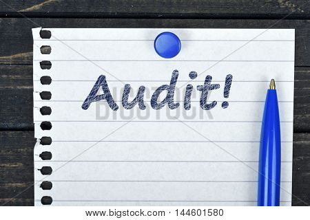 Audit text on page and pen on wooden table