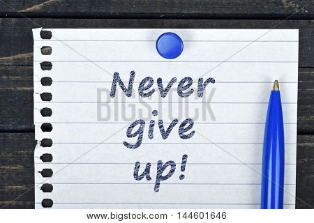 Never give up text on page and pen on wooden table