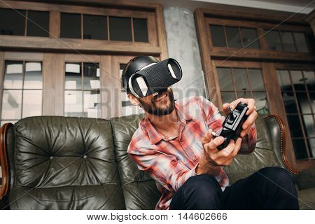 Young man playing video games in virtual reality headset. Male adult with joystick and vr glasses controlling vehicle while playing. Modern technology, innovation, cyberspace, entertainment concept