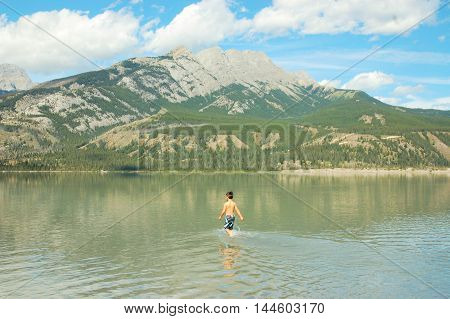 boy wandering and wading through water lake mountains and sky in background canadian rockies