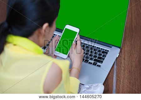 Back view of woman's hands using smart phone and laptop computer on floor wooden. Green screen on phone and laptop computer. Shallow depth of field, phone in focus. People and technology concept.