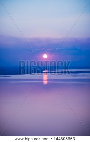 Fantastic seascape with cool sunset background. Abstract beautiful sunrise over the sea. Bright seascape during sundown with reflection of sun. Outdoor. Cool colors tone effect.