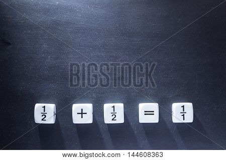 white fraction mah number dices showing simple equation half plus half equal whole on blackboard good for background and teaching blogs with harsh lighting showing long dices' shadows and selective focus on dices room for copyspace on top of frame