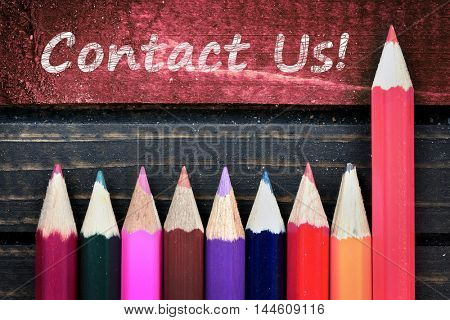 Contact Us text and group of pencil on wooden table