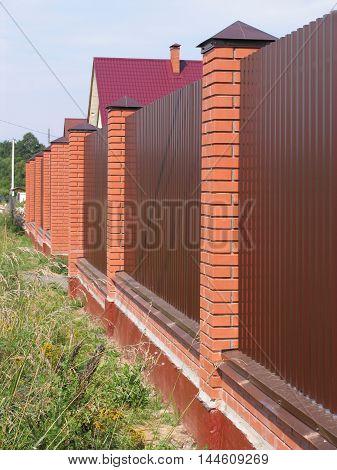 Metal fence with brick pillars around cottage